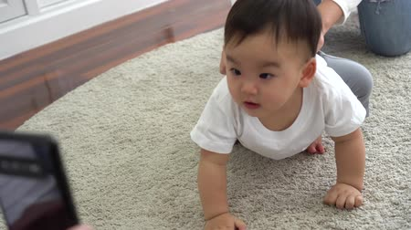 Parent using smartphone to shoot video of cute Asian baby crawling on soft white carpet at home.