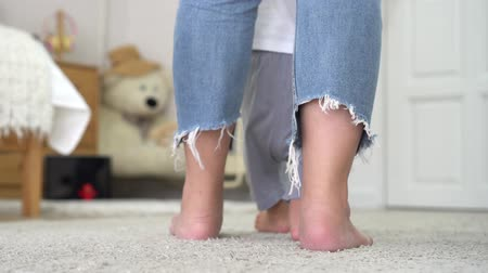 Barefoot woman in jeans teaching little baby to walk on soft white carpet in cozy nursery at home.
