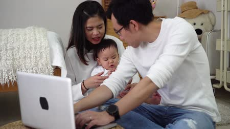 Asian father working using laptop with his wife and cute Asian baby boy while sitting on floor in cozy room at home. Wideo