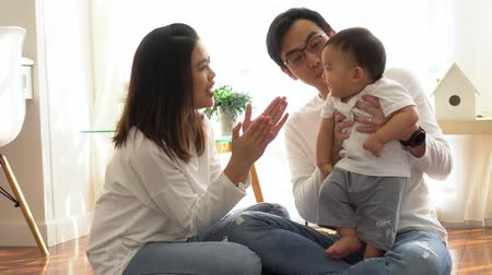 Happy Asian family of three, young father and mother playing games and clapping hands with baby boy child at home, parents enjoying family time.