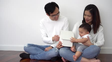 Cheerful Asian ethnic mother and father smiling and showing toy house to cute baby while sitting crossed legged on floor near white wall at home.