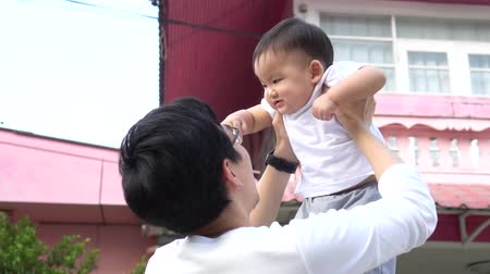 Loving father lifting happy Asian baby and playing with child while standing in front of their house. Wideo