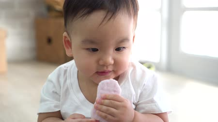 Cute Asian baby biting piece of snack while sitting on floor in cozy room at home.