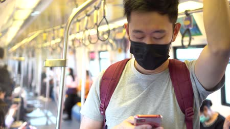 longontsteking : Close up of one young Asian man wearing a black surgical face mask and using mobile phone in subway train during new type Coronavirus Covid-19 pneumonia outbreak and pm 2.5 smog air pollution crisis Stockvideo