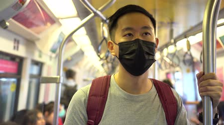 longontsteking : Close up of one young Asian man wearing a black surgical face mask in subway train during new type Coronavirus Covid-19 pneumonia outbreak and pm 2.5 smog air pollution crisis in big city.