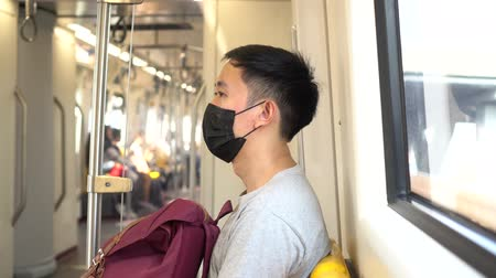 Close up of one young Asian man wearing a black surgical face mask in subway train during new type Coronavirus Covid-19 pneumonia outbreak and pm 2.5 smog air pollution crisis in big city.