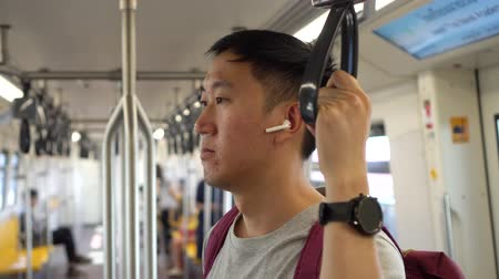 Close up of young man listening to music with wireless earpods while commuting by train. Asian guy enjoying music on the go