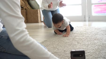 захват : Parent using smartphone to shoot video of cute Asian baby crawling on soft white carpet at home.