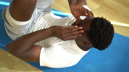 Young African American man doing sit-up exercise on yoga mat at gym. Male fitness model performing crunch at fitness center.