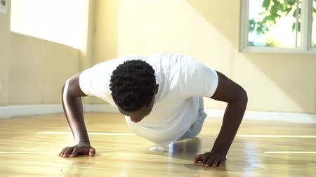 Young African American man doing push-up on the floor. Determined male fit sportsman exercising during workout.