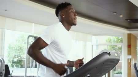 From below fit African American man running on electric treadmill in gym on daytime. Sportsman working out on training machine.
