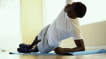 Athletic African American man balancing on one arm while doing side plank exercise on mat in gym.