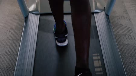 afro americana : African American sportsman in blue sneakers working out on electric treadmill in fitness club. Faceless male runner running on treadmill. Stock Footage