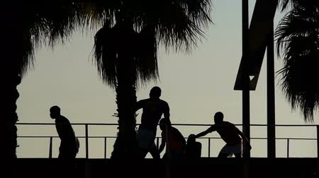 jogador de futebol : silhouettes of football players on a beach at sunset