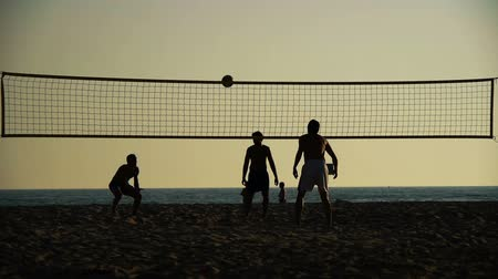 volleyball : silhouettes of volleyball players on a beach at sunset