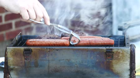 grilling : Tongs Turn Hot Dogs On A Small Grill