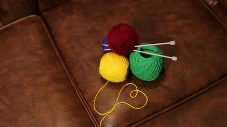 přadeno : Knitting yarn with knitting needles lying on the leather sofa. Dostupné videozáznamy