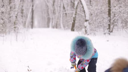 родной брат : Two small children play with snow in winter Park.