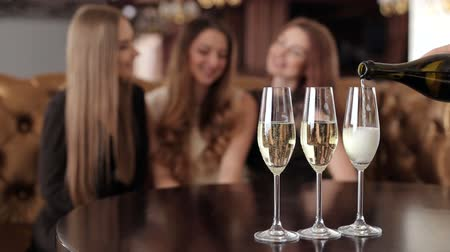 três pessoas : The waiter pours champagne for the three girls in the restaurant.