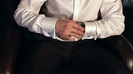 üzleti öltöny : Businessman in white shirt with cufflinks looks at the clock close up.