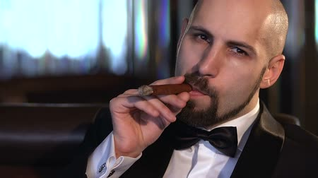 adam : Brown-eyed bald man Smoking a cigar and looking at the camera, slow motion.