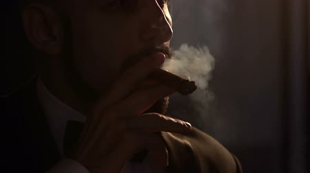 cigar : Silhouette of bearded Caucasian man who smoking a cigar, slow motion.
