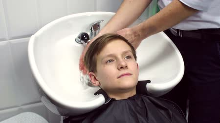 şampuan : Barber washes the head of the boy in the barbershop, slow motion.