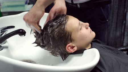 mycie rąk : Male hairdresser washes the hair of a boy in a hairdresser, slow motion.