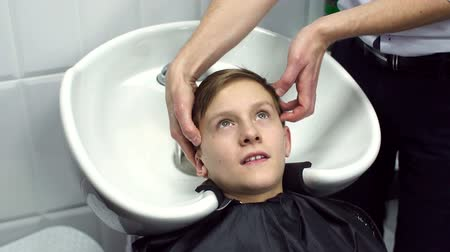 mycie rąk : The stylist washes the hair of the young guy in the beauty salon, slow motion.