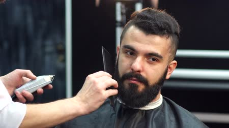 борода : Portrait of a bearded man in a barbershop. The hairdresser combs clients beard in the hairdressers. Стоковые видеозаписи