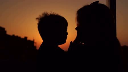 país : Silhouette of a little boy who kisses his mother at sunset, slow motion. Portrait mom and baby at sunset.