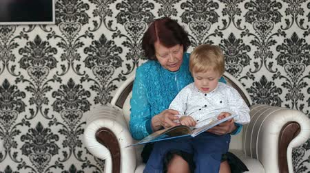 biblia : Happy grandma and little boy sitting on sofa and reading book.