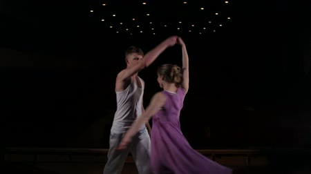 moderní : Young couple dancing contemporary on stage in the dark.