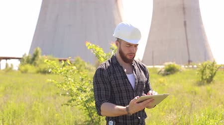 primeiro plano : Engineer in a plaid shirt and a white hard hat working on the tablet outdoors. Stock Footage