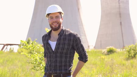 компания : Portrait of cheerful bearded handsome young adult industrial engineer with plastic helmet look at camera on the background of the heat power plant.