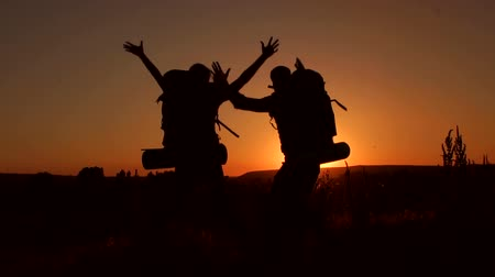 alpinista : Silhouette of two hikers with backpacks Bouncing with joy after a hard ascent to the top of the mountain. Slow motion. Climbers jumping for joy after a hard climb. Stock Footage