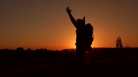 Silhouette of a traveler with a large backpack lifts hands to the sky standing on top of a mountain at sunset, slow motion. Dostupné videozáznamy