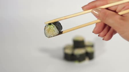 gunkan : Womans hand holding fresh sushi roll by wooden chopsticks, isolated on white background.