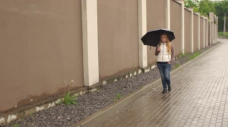 andar : Young girl walking with umbrella under the rain beside a long high wall, slow motion. Girl with long blond hair under an umbrella walks in the Park. Vídeos