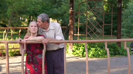 lasting : Grandpa kisses the old woman in the Park standing in a large gazebo. Caring grandpa kisses his old wife.