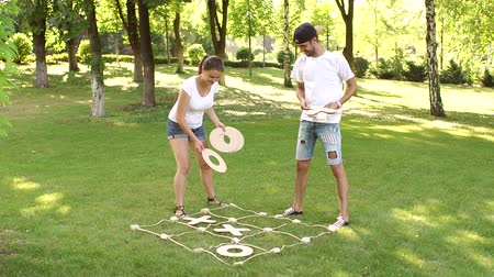tık : Two young people play the game tic tac toe big pieces in the Park in the summer. Large outdoor games.