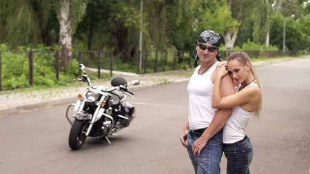 undershirt : Pretty brutal couple of bikers standing in an embrace on the big motorcycle on the road. Stock Footage