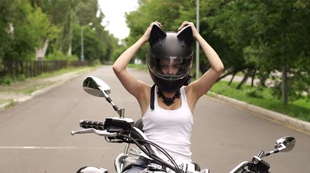 undershirt : Young sexy girl sitting on a motorcycle and puts on her head a protective helmet with cat ears.