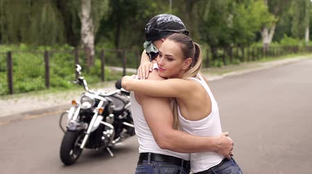 undershirt : Loving couple in white undershirt standing in an embrace on the big fashionable motorcycle on the road in the countryside.