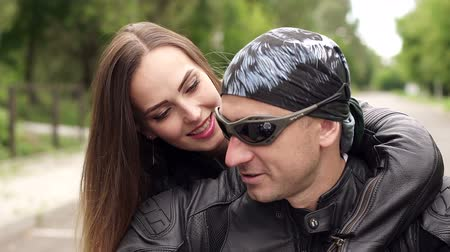 undershirt : Close-up of loving couple in leather jackets and bandana sitting on a motorcycle. Stock Footage