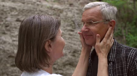 bochecha : Older woman gently stroking her beloved husband in the face on the stone wall background. Close-up. Slow motion.