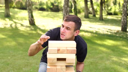 ga : Funny guy ridiculously removes a non-existent speck of dust from the large wooden blocks of the childrens game.