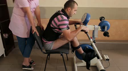física : Rehabilitation for man with a broken back. Young man with a broken spine undergoing rehabilitation at the physiotherapists office on robotized bike. Kinesitherapy on motomede.
