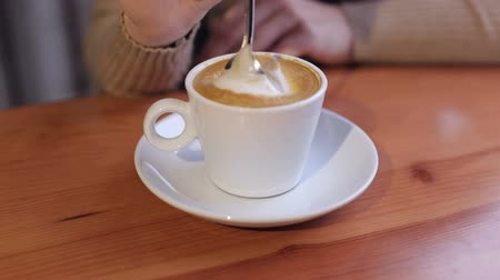 jumble : Close-up of a girl is stirring a cappuccino spoon while sitting at a table in a cafe.