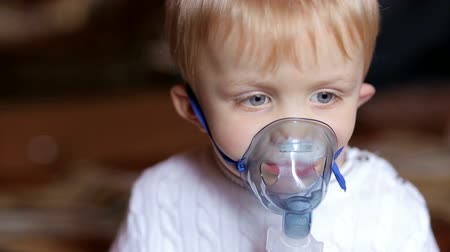 asthma : Little blonde boy of three - four years is treated with a nebulizer, cough. Small boy does therapeutic inhalation using a nebulizer. Stock Footage